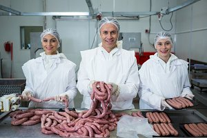 Butchers packing sausages at meat factory