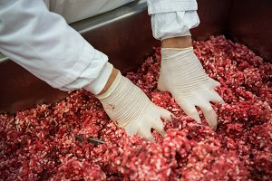 Butcher mixing minced meat in meat factory
