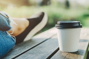 White cup of coffee at sunny park