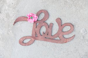 Wooden handwritten sign love on concrete