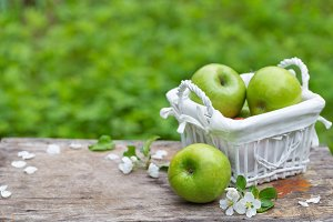 Fresh sweet juicy green apples with flowers wood
