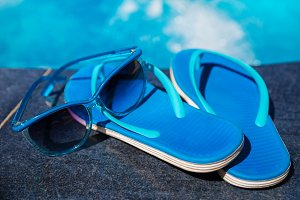 Blue slippers and sun glasses near swimming pool