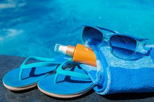 Sunglasses sunscreen cream blue slippers towel