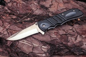 Pocket knife in the unfolded form on the background of pine. A sharp knife.