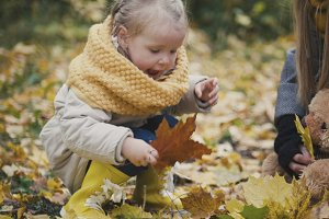 Little girl plays with leaves in autumn park