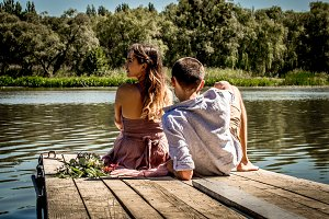 beautiful young couple on the pier near the river