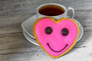 tasty cookies in the shape of a heart with Cup tea