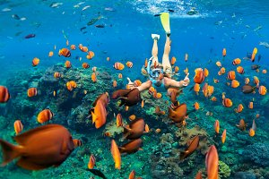 Snorkelling girl with reef fishes