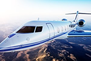 Image of White Luxury Generic Design Private Jet Flying in Blue Sky at sunset.Uninhabited Desert Mountains Background.Business Travel Picture.Horizontal,Film Effect. 3D rendering.