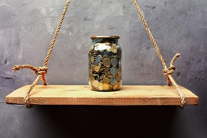 Glass jar with coins on the shelf
