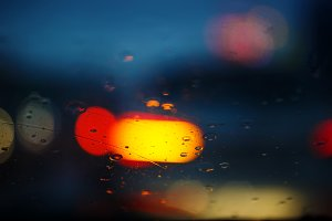 Rain drops on car glass with traffic light , focus on raindrops