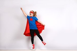 Six year blonde girl dressed like superhero having fun at home.