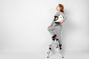 Happy child girl dressed in an astronaut costume standing on stepladder