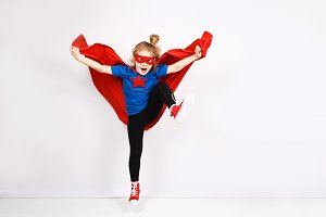 Six year blonde girl dressed like superhero having fun at home. White wall on background