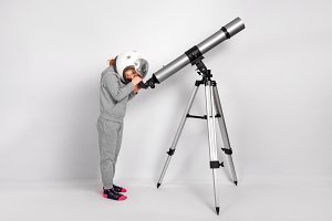 Happy child girl dressed in an astronaut costume looks through a big telescope