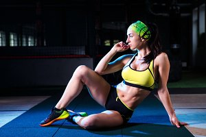 beautiful, sporty girl is sitting in the gym. Dark background. Dressed in shorts and a t-shirt with a bandage on his head. Sports concept.