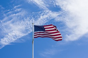 US flag on blue sky with cloud