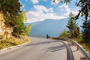 A man stands next to a Bicycle on the mountain road. Summer in the mountains of Bulgaria
