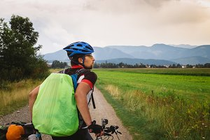 the guy on the Bicycle travels in Slovakia. Blue helmet, green backpack, glasses,