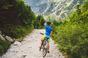 girl on a Bicycle travels to Slovakia. black helmet, blue shirt, mountains, high Tatras,