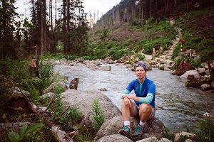 girl tourist Sedin on the stone near the mountain river in high Tatras in Slovakia. Dressed in a blue t-shirt, gray shorts, Hiking boots