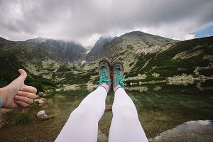 the view of the mountains, the feet of camper shoes, hand thumbs up