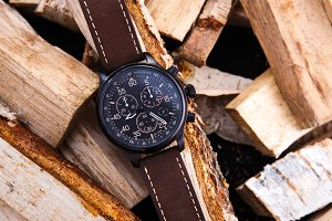 wrist watch men's brown leather strap on wood.
