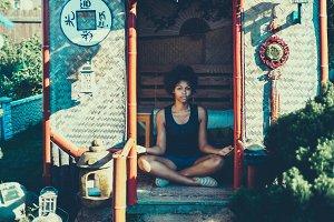 Black girl meditating in pagoda