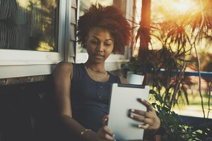 Black curly girl with digital tablet
