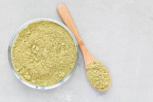 Matcha tea powder on the a plate and in wooden spoon, top view, copy space