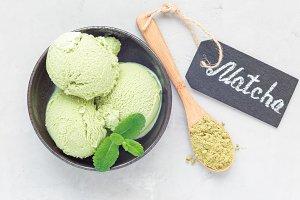 Matcha green tea ice cream balls in black bowl, horizontal, top view