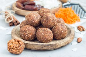 Healthy homemade paleo energy balls with carrot, nuts, dates and coconut flakes, on wooden plate, horizontal