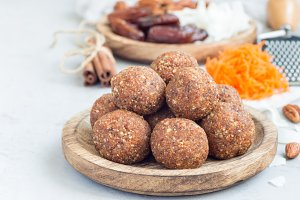 Healthy homemade paleo energy balls with carrot, nuts, dates and coconut flakes, on wooden plate, horizontal, copy space