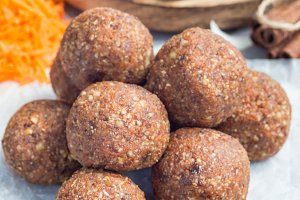 Healthy homemade paleo energy balls with carrot, nuts, dates and coconut flakes, on parchment, vertical