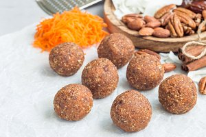 Healthy homemade paleo energy balls with carrot, nuts, dates and coconut flakes, on parchment, horizontal, copy space