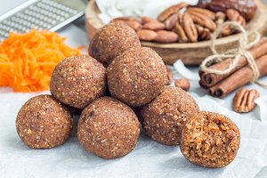 Healthy homemade paleo energy balls with carrot, nuts, dates and coconut flakes, on parchment, horizontal