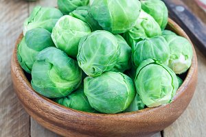 Fresh brussels sprouts in bowl on wooden background, vertical