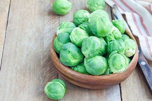 Fresh brussels sprouts in bowl on wooden background, horizontal, copy space