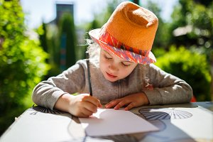Cute little girl in straw hat, spring outdoor.