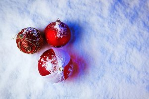 Ornate christmas balls in snow with blue backlight.