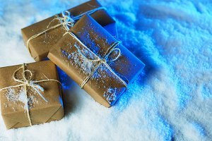 Handmade gift boxes from craft paper over snowy wooden table in blue light.