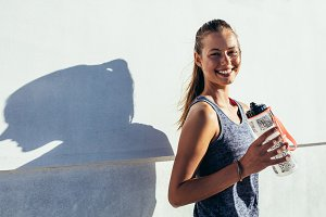 Happy female runner holding water