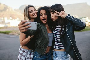 Happy friends making selfie