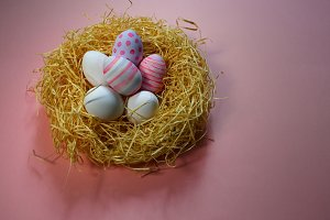 Colorful vintage easter eggs in nest on pink background