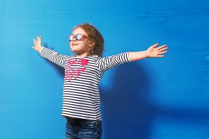 Happy child girl tourist in pink sunglasses at the blue wall. Travel and adventure concept
