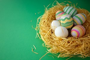 Colorful vintage easter eggs in nest on green background