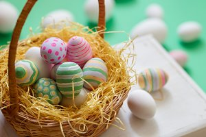 Basket with colorful Easter eggs, close up photo