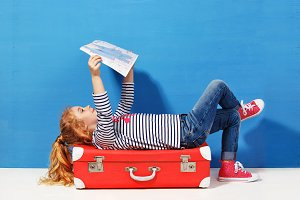 Child blonde girl with pink vintage suitcase and city map ready for summer vacation. Travel and adventure concept