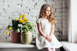 Little blonde girl in a white dress sitting by the window