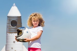 Portrait of blonde little girl in an astronaut costume with toy rocket dreaming of becoming a spacemen